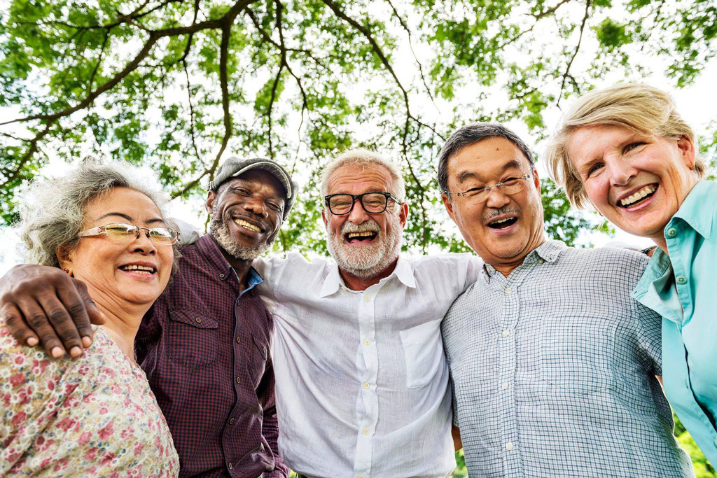 Group of people smiling under tree
