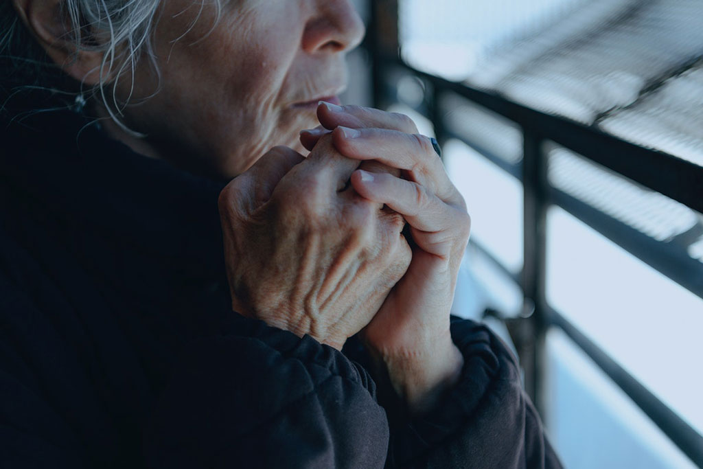 Elderly woman holding her hands together tight