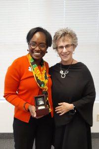 2 women holding an award smiling