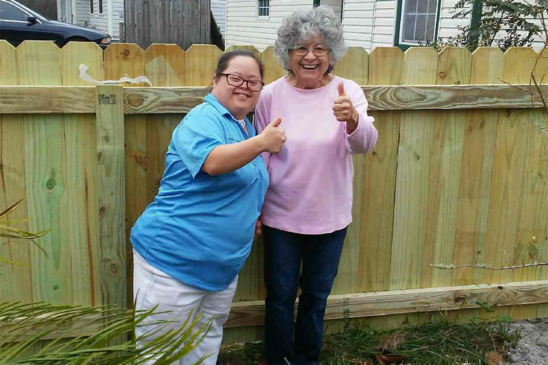 2 women in front of fence