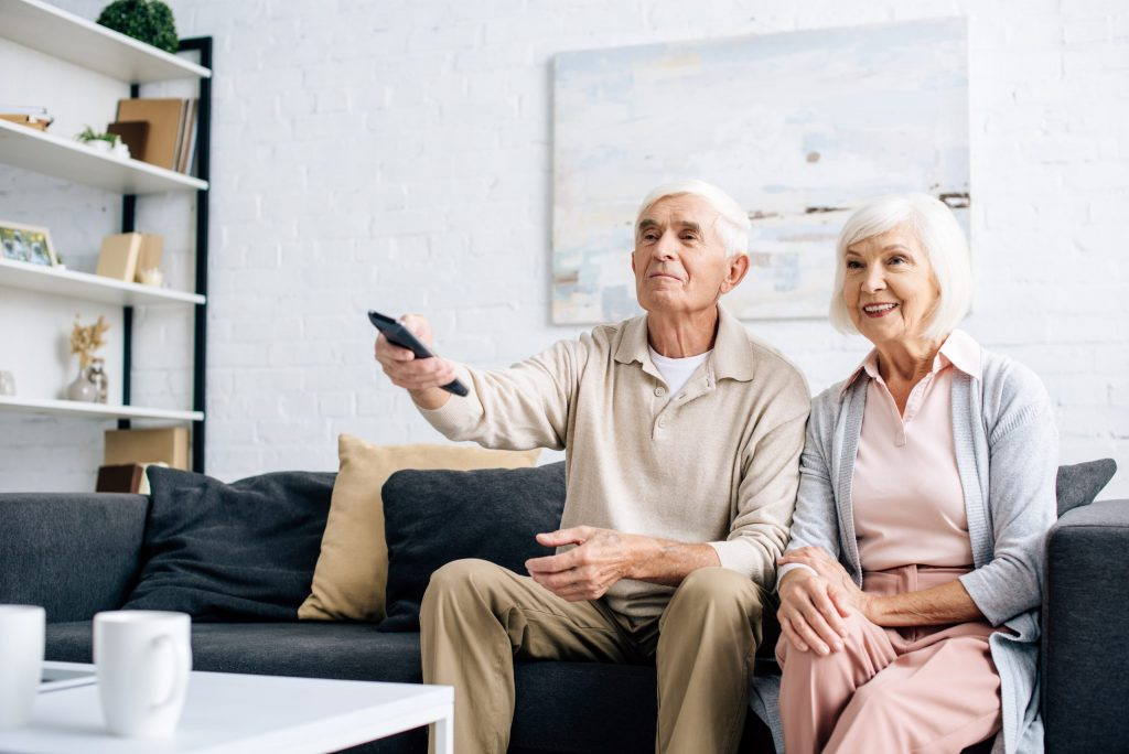 smiling husband and wife watching tv and sitting on sofa in apartment